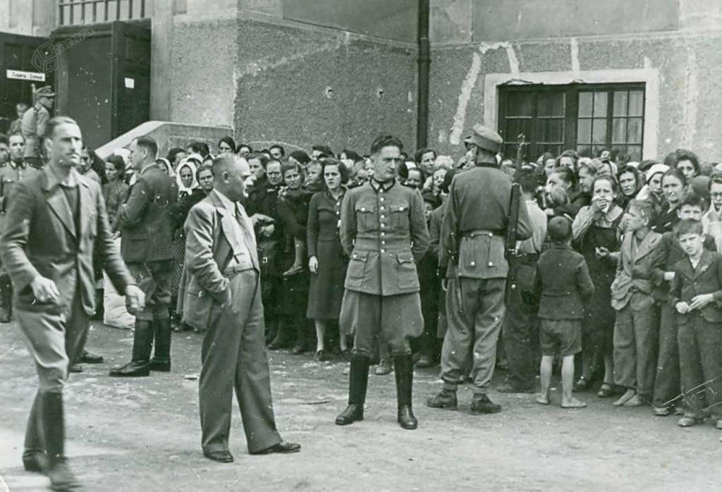 Komandant nemške varnostne službe in policije na Spodnjem Štajerskem Otto Lurker (drugi z leve v civilni obleki) pred množico aretiranih žena in otrok iz uporniških družin, Celje, avgust 1942