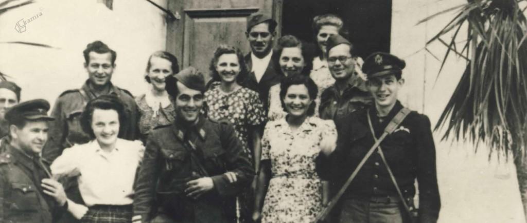 Načelnik štaba Četrte operativne cone Petar Brajović v družbi soborcev ter domačink. Prvi z leve je vodja sovjetske vojaške misije Jurij Bogomolov, prvi z desne pa vodja anglo-ameriške vojaške misije Franklin A. Lindsay, Gornji Grad, avgust 1944
